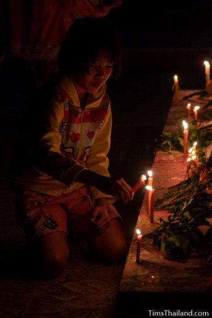girl putting candles around the base of a stupa