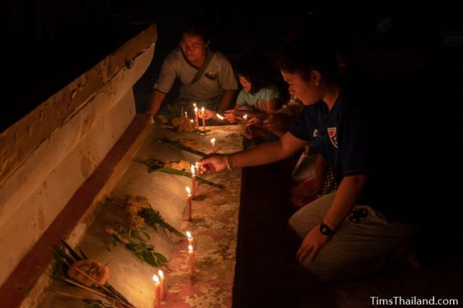 people putting candles around the base of a stupa