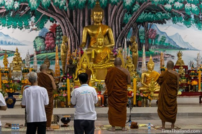 monks standing in front of Buddha image