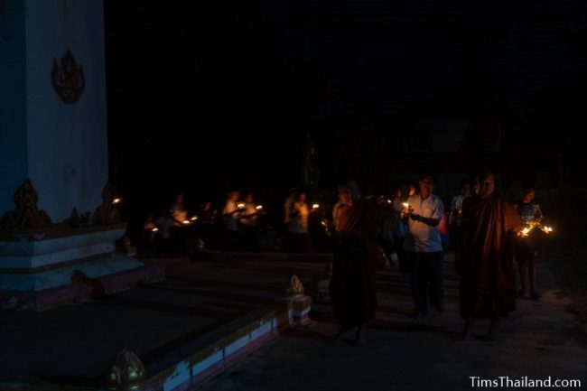 people holding candles walking around a stupa