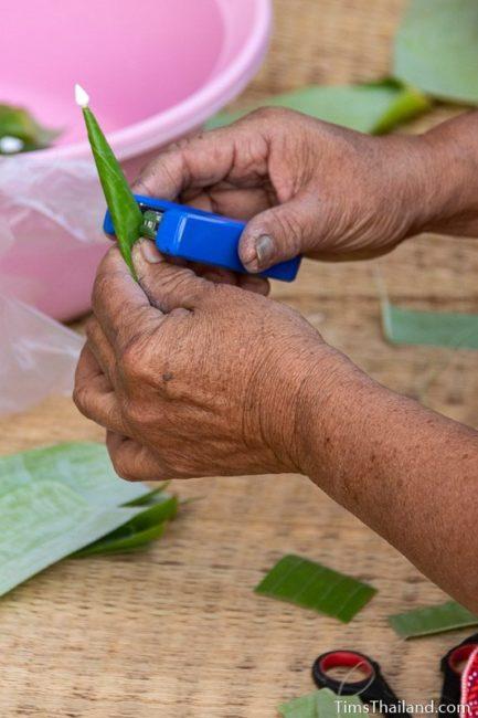 closeup of woman stapling banana leaf to make bai sii