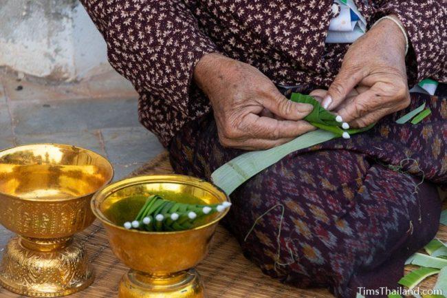 closeup of woman making bai sii
