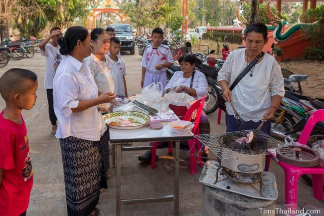 women making khao griap at the temple