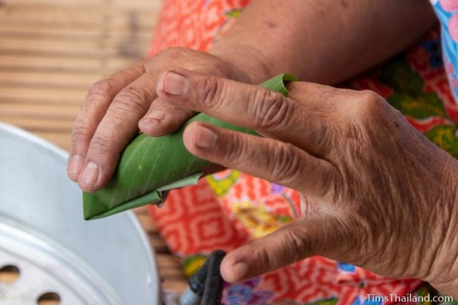 closeup of woman making khao tom mat