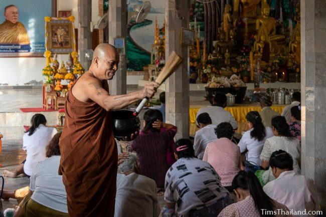 monk blessing people by splashing water