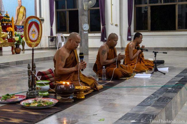 monks holding sai sin sacred thread