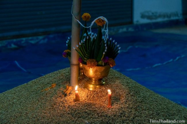 lit candles and bai sii on top of rice pile