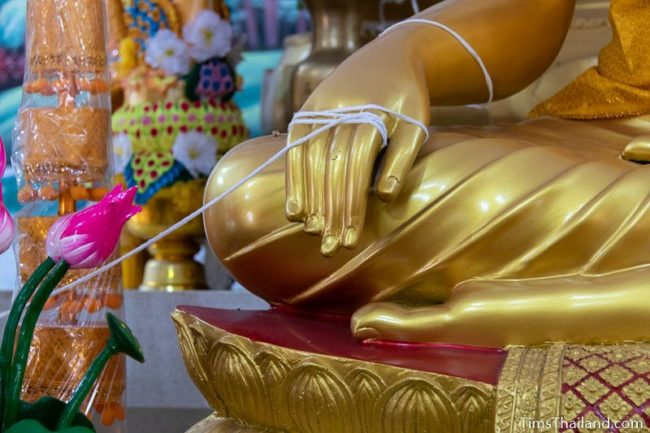 sai sin sacred thread wrapped around the hand of a Buddha