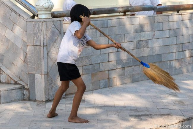 girl sweeping in front of temple