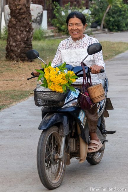 woman driving motorcycle with flowers on the front
