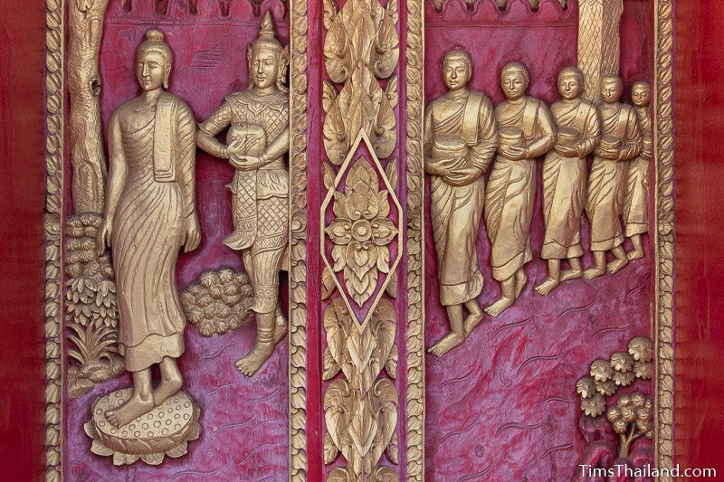 woodcarving of the Buddha walking with many disciples