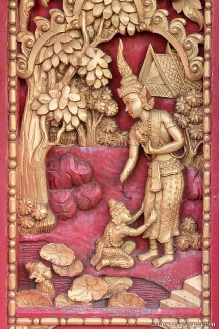 woodcarving of child crying at father's feet.