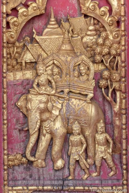 woodcarving of family riding on back on elephant.