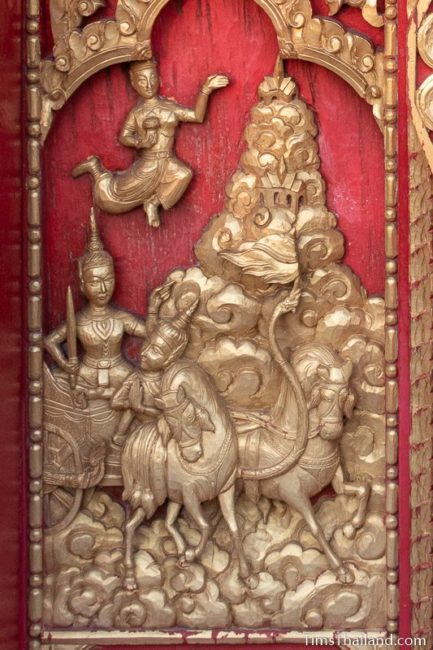 woodcarving of chariot riding through heaven.