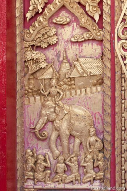 woodcarving of man riding an elephant.
