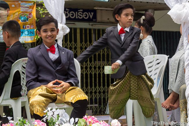 two boys in suit coats in a Khao Phansa candle parade