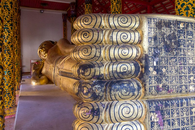 large reclining Buddha in Entering Nirvana posture with designs painted on soles of feet