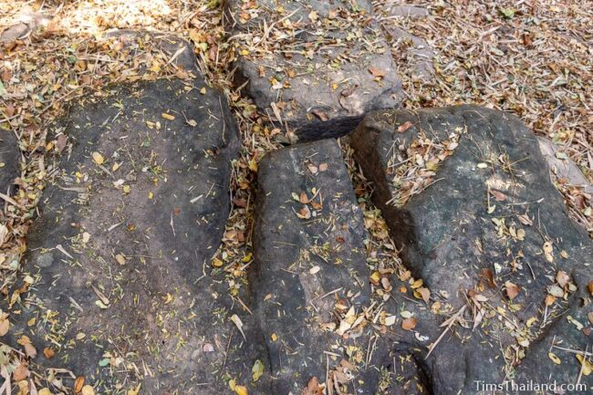 rock outcrop with blocks cut out of it
