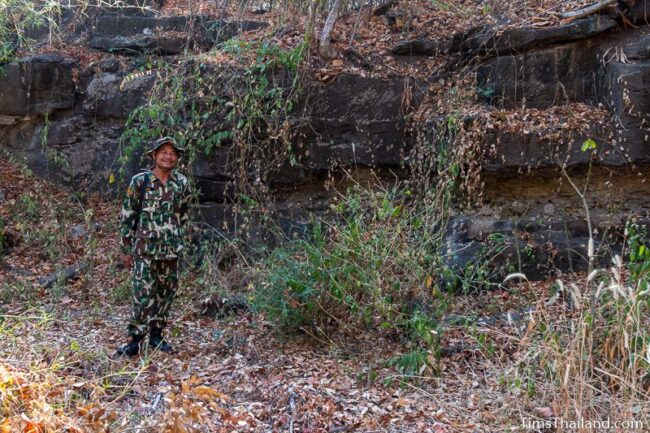 park ranger standing in front of a rock wall with cut marks