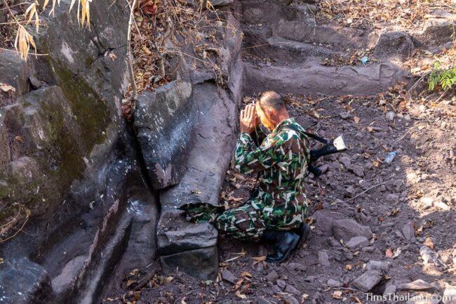 park ranger making offering at rock outcrop with blocks cut out of it