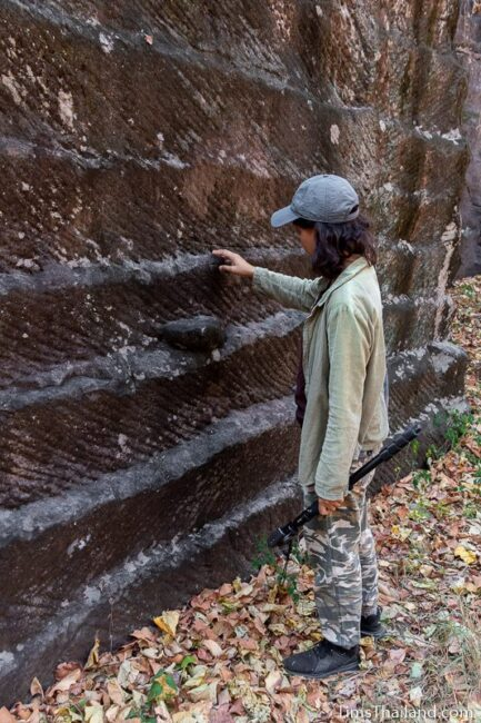 woman looking at rock wall with cut marks