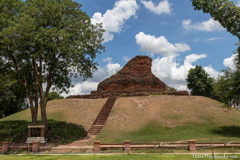 ruined brick stupa on a hill seen from below