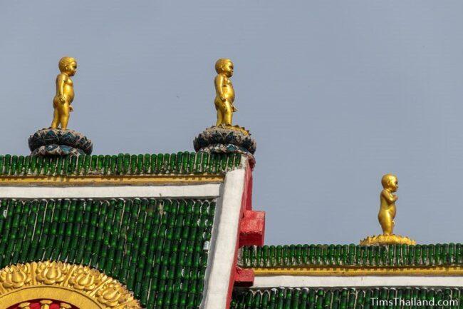 Baby Buddha statues on roof peak of ubusot
