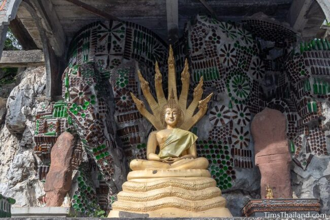 Buddha with bottle art behind it