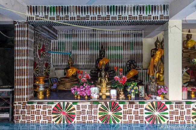 Buddha shrine with bottle art around it