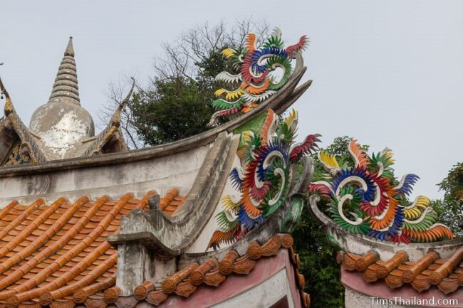 Chinese decoration on top of roof and a stupa in the background
