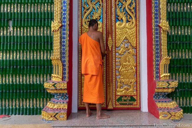 monk unlocking door to ubosot