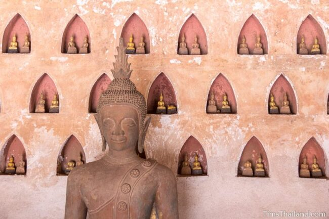 large Buddha in front of wall with smaller Buddhas in little alcoves