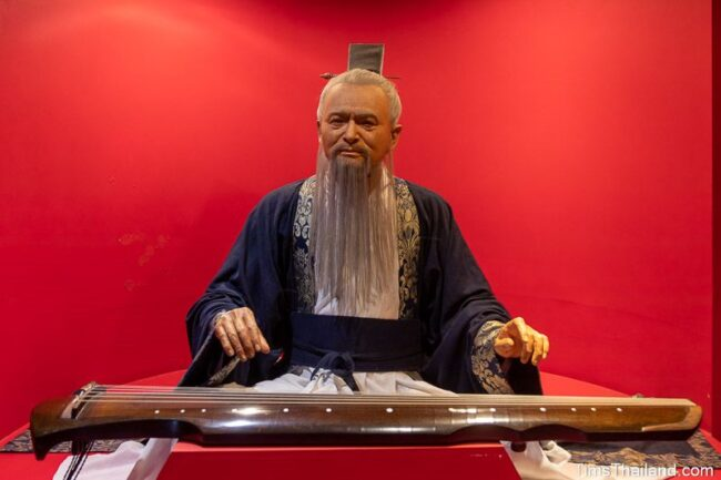 life-like statue of Confucius playing a guqin