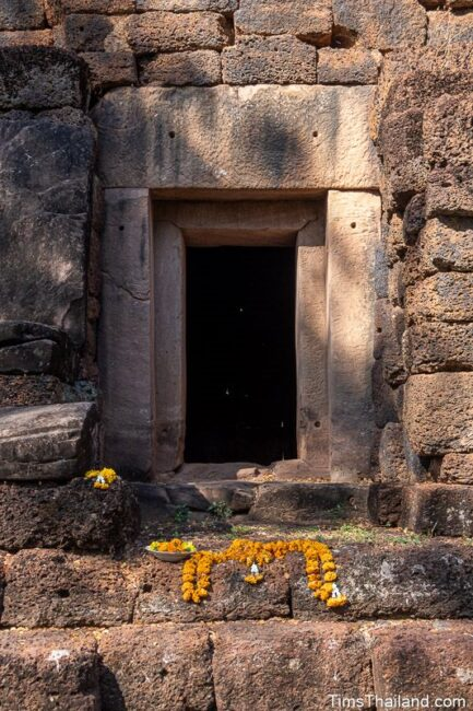 front door of prang with flower offerings on steps