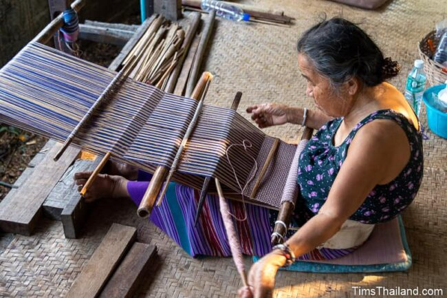old woman weaving with backstrap loom