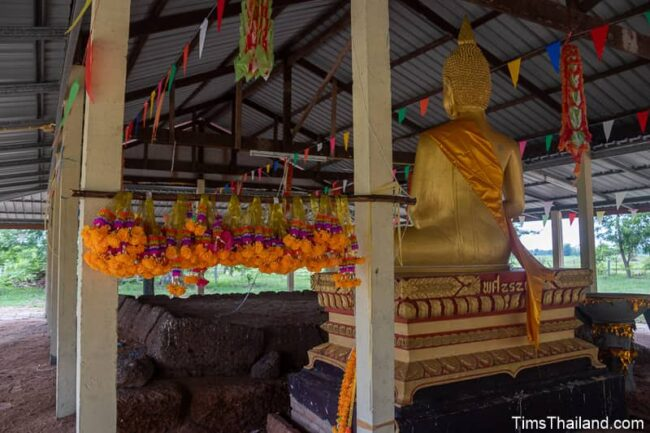flower offerings next to Buddha in front of Khmer ruin