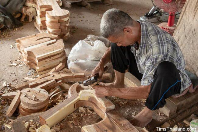 man carving wood