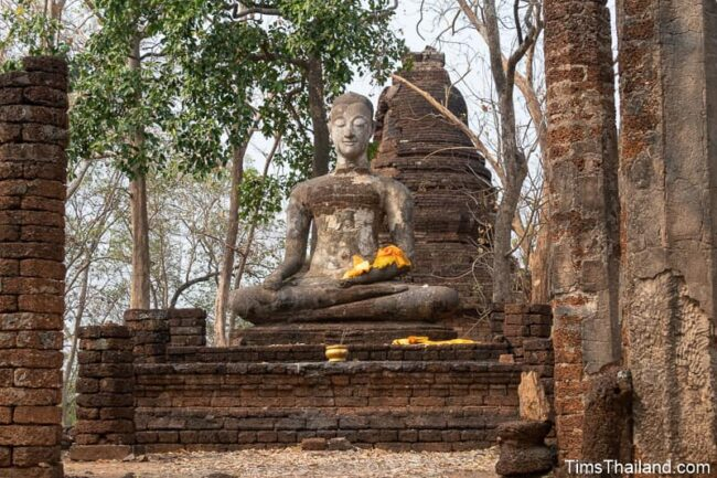 Buddha statue in front of ancient stupa
