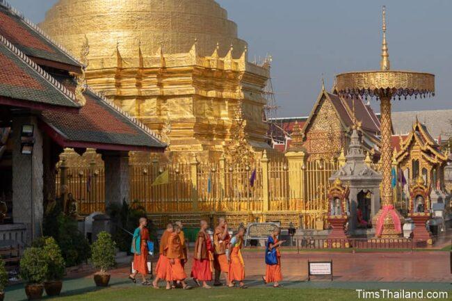 novices walking in front of stupa