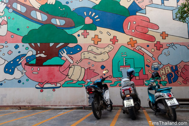 motorcycles parked in front of large mural